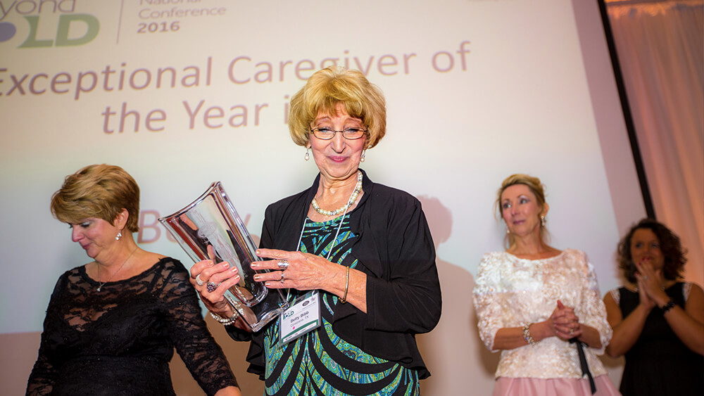 Betty holding a trophy at the Exceptional Caregiver of the Year 2016 Conference