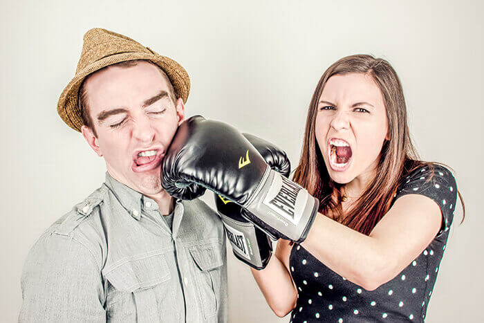 A woman wearing boxing gloves pretending to punch a man in the face