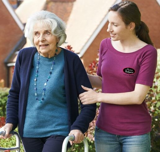 Home Helpers Caregiver holding an elderly woman as they walk