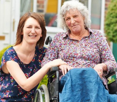 Woman smiling while sitting next to an elderly woman on a wheelchair
