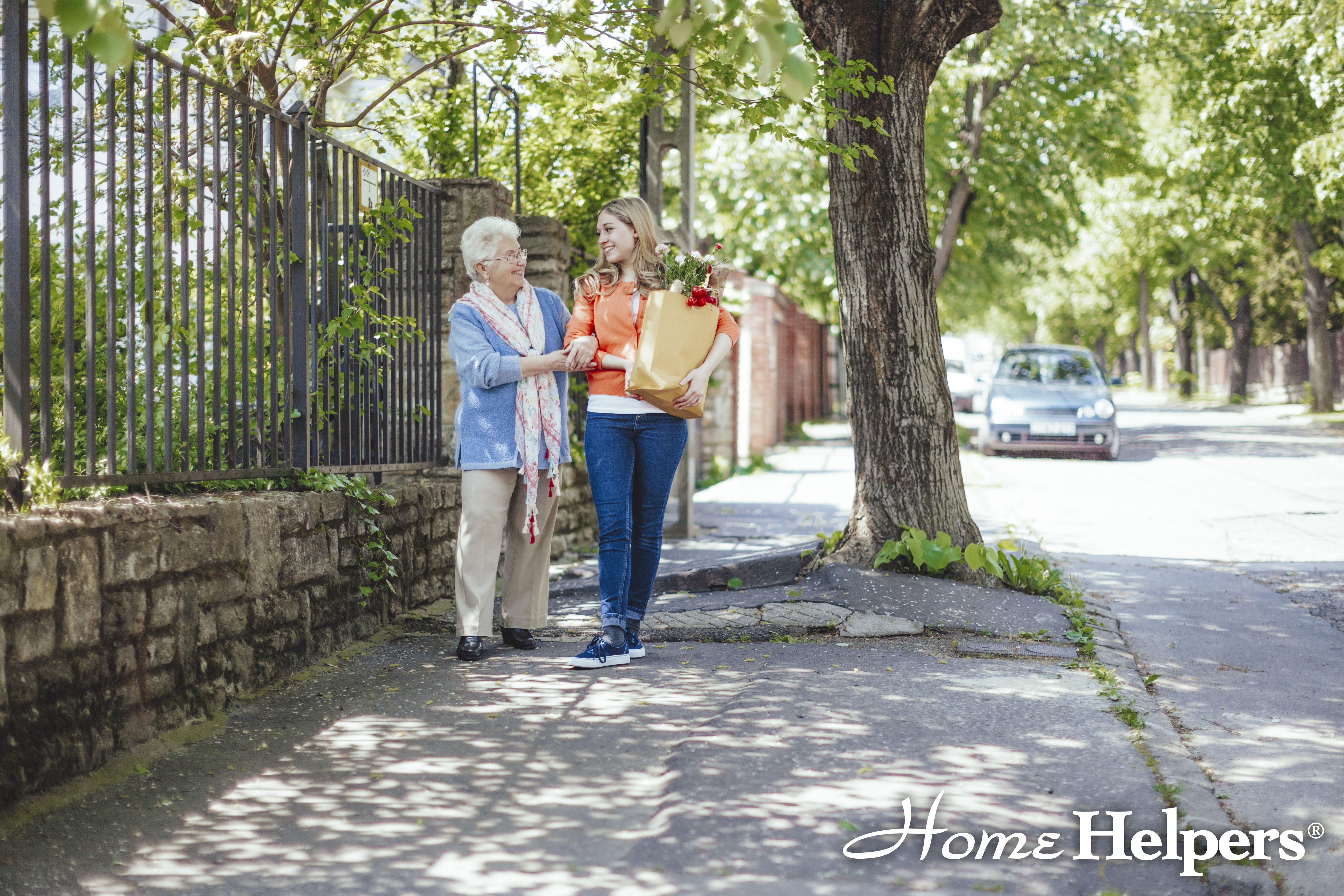 Home Helpers caregiver and client walking home with grocery bags