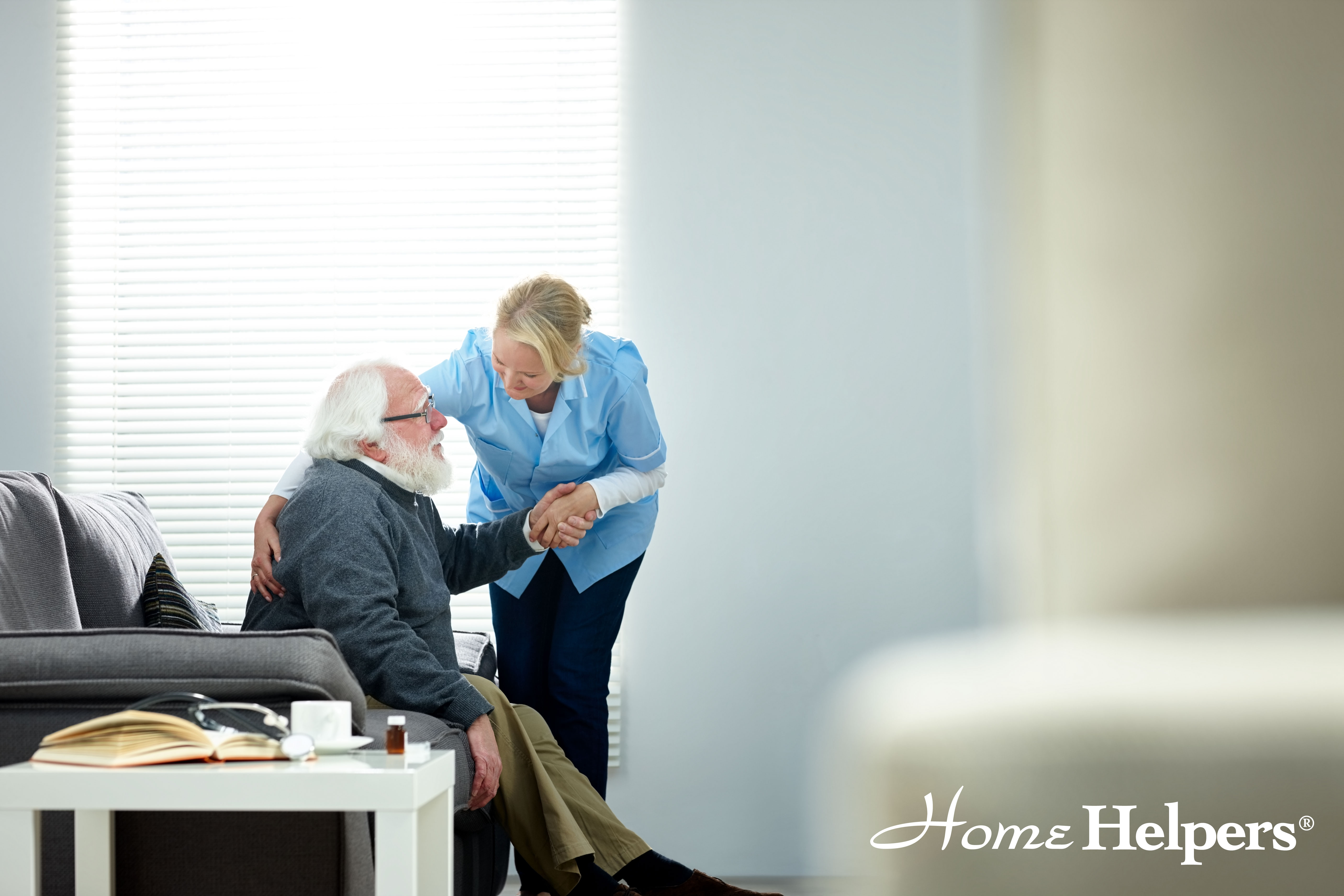 Home Helpers caregiver helping client out of a chair