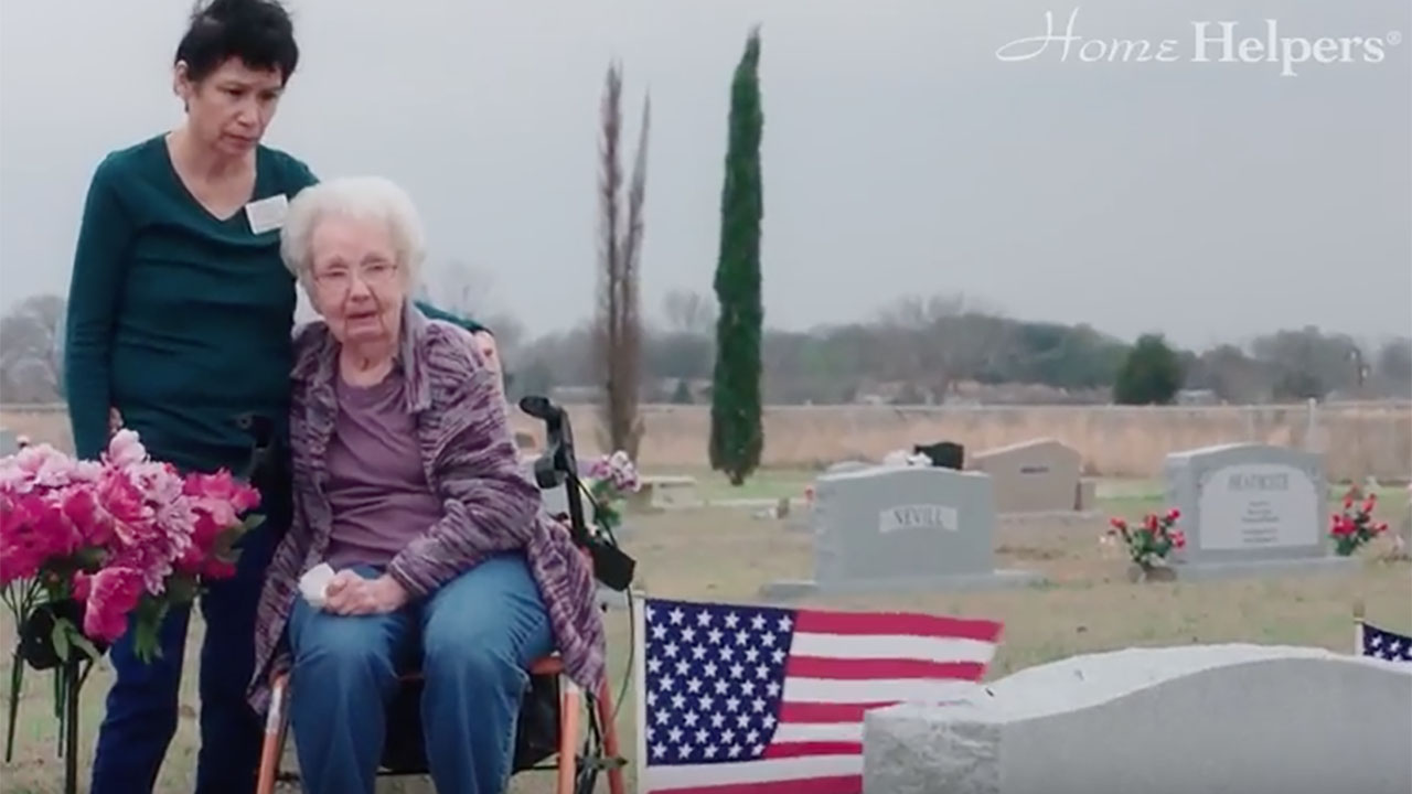 Home Helpers caregiver paying respects with client at cemetery