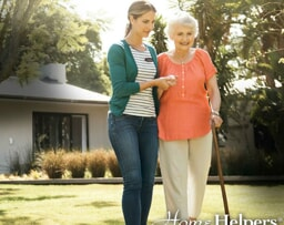 caregiver walking across lawn with senior woman