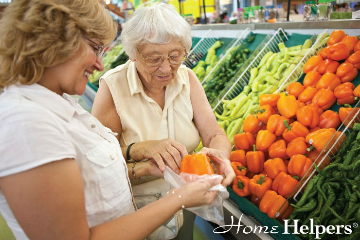 Woman helping senior woman bag a vegetable at supermarket