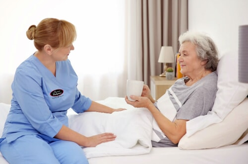 caretaker speaking to senior in bed holding teacup