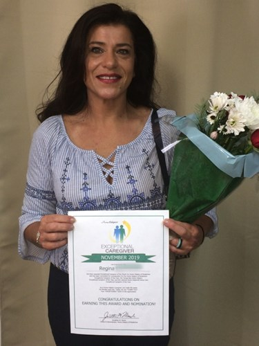 Regina Holding an Exceptional Caregiver Certificate